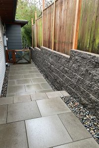 Gray architectural slab pavers with fence on top of block wall