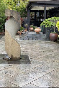 Beautiful scenic backyard paver patio with modern sculpture