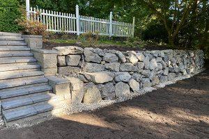 Terraced rockery retaining wall with block steps leading to backyard garden
