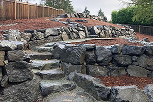 Terraced rockery walls and steps on steep slope in backyard of Seattle house
