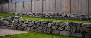Backyard terraced rockery and pavers with grass on multiple levels