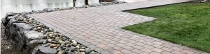 Paver pathway on top of rock retaining wall by lakeside property