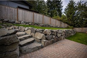 Backyard hardscape with rockery steps, rockery walls, and Holland pavers