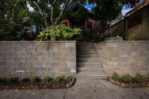 Rustic staircase framed by Manorstone block wall and plants