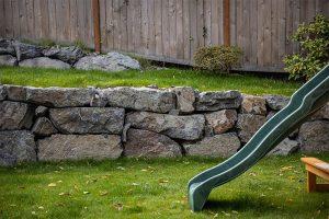 Landscaped backyard playground with rockery retaining wall