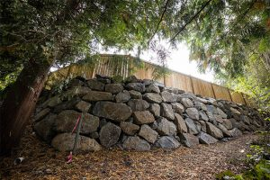 Curved rockery wall with fence on top in Seattle