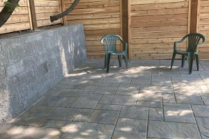 Columbia slate pavers with pattern design surrounded by block wall and cedar fence