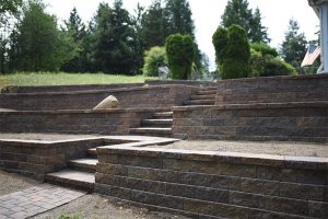 Multi-terraced retaining wall with steps, pavers, and accent boulder