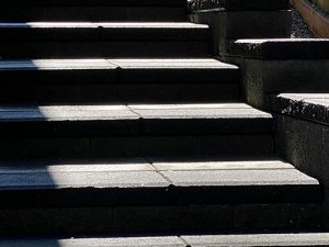 Shadows on block wall steps with charcoal capstones and pavers