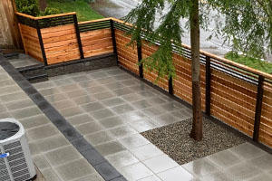 Full hardscaped front yard with fence, block walls, and pavers in a Seattle neighborhood