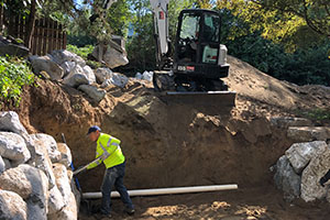 Excavation site preparation for installing rockery retaining wall with drainage