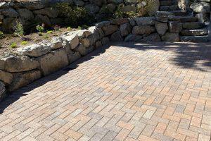 Red brick pavers with herringbone pattern between terraced rockery wall and rockery steps