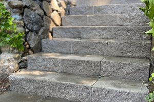 Cement block steps with scenic rock wall and greenery