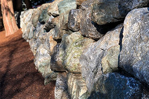 Engineered rockery retaining wall near tree
