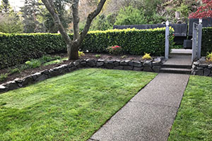 Rock garden wall with lawn and pathway to gate