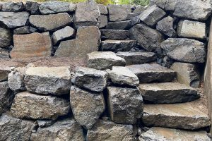 Terraced basalt rockery retaining wall with curved steps