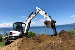 Seattle Rockeries excavator leveling and grading at home near Puget Sound