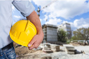Man holding yellow safety helmet at a construction site