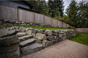 Rockery wall with steps leading down to pavers